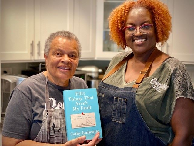 Two Women Hold Book to Action title
